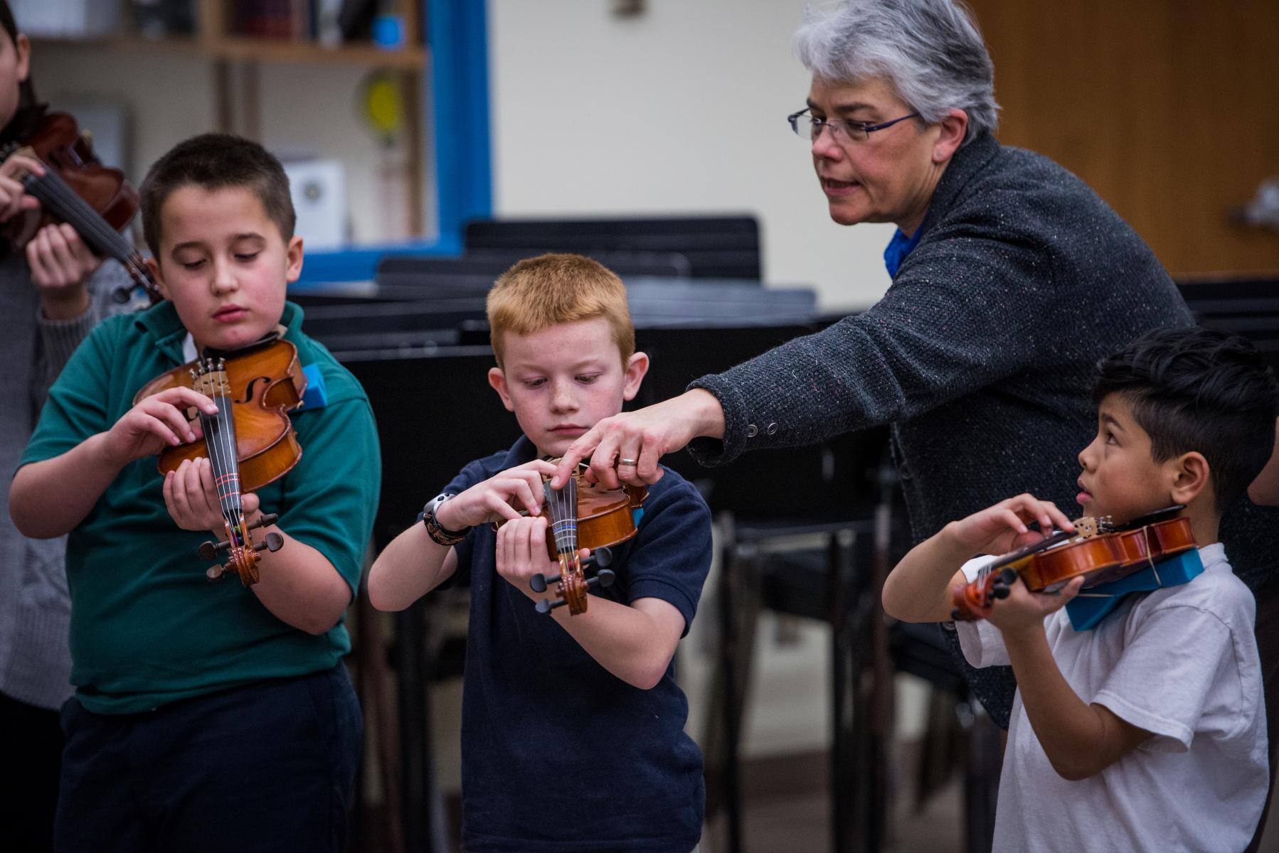 Teacher with a students violins