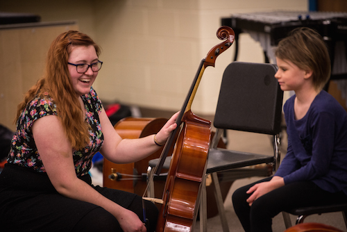 Teacher with a student with a cello