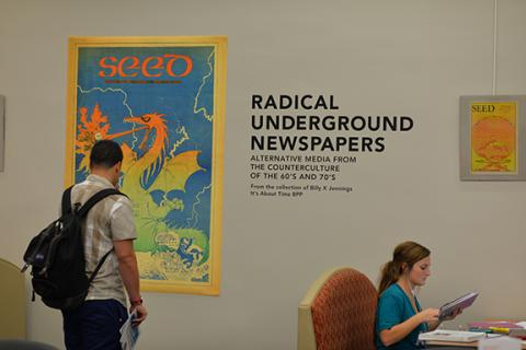 Students browse the underground newspapers exhibition in Love Library. Photo by Michael Reinmiller.