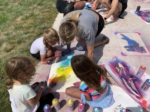 Students in Alliance create spray chalk animals as part of the Stay Wild community arts project, led by Associate Professor of Art Sandra Williams. Courtesy photo.