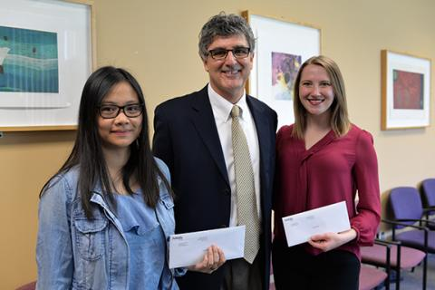 Dean Charles O'Connor presents awards to Emily Tran (left) and Taylor Mead.