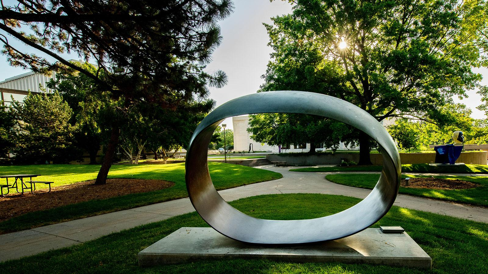 large outdoor sculpture in an oval shape with the sunrise shining through green trees