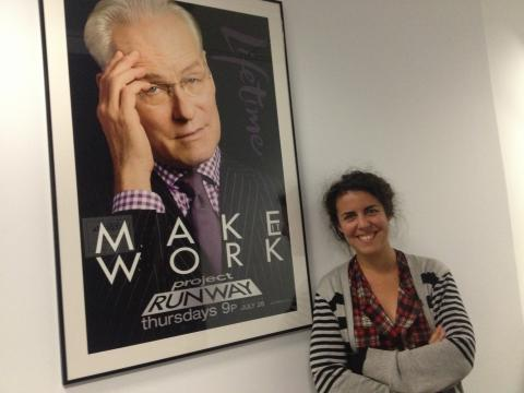 Josie Azzam portrait at work next to Project Runway poster