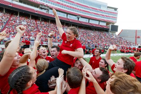 """Sophia Kallas of Green Bay, Wisconsin, is held aloft by fellow Cornhusker Marching Band members after winning the """"drill down"""" competition during the 2018 exhibition. The 2019 event is 7 p.m. Aug. 23. Photo by Craig Chandler, University Communication."""