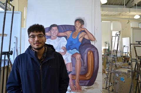 """Luis Martinez stands in front of his painting titled """"Flojeando,"""" in the Richards Hall painting studio."""