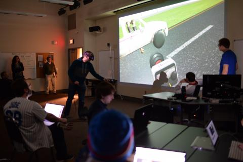 Film and New Media Senior Ben Hartzell (in VR goggles on left) shows the progress of his team's final project in class on April 10. Photo by Michael Reinmiller.