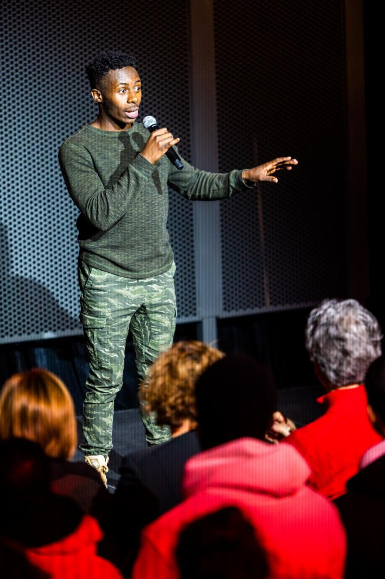 Jean-David Bizimana shares his story during the performance. Photo by Justin Mohling.