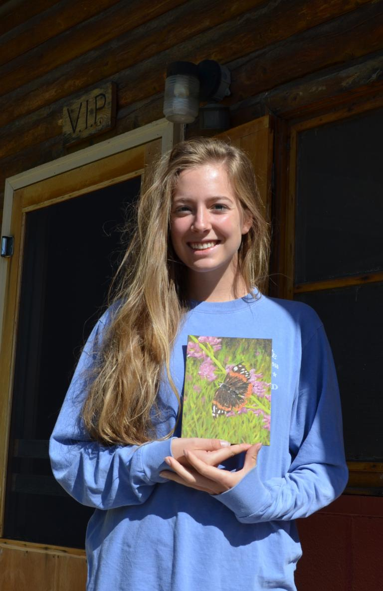 Mariah Livingston, a junior art major, shows off one of her paintings created at Cedar Point.