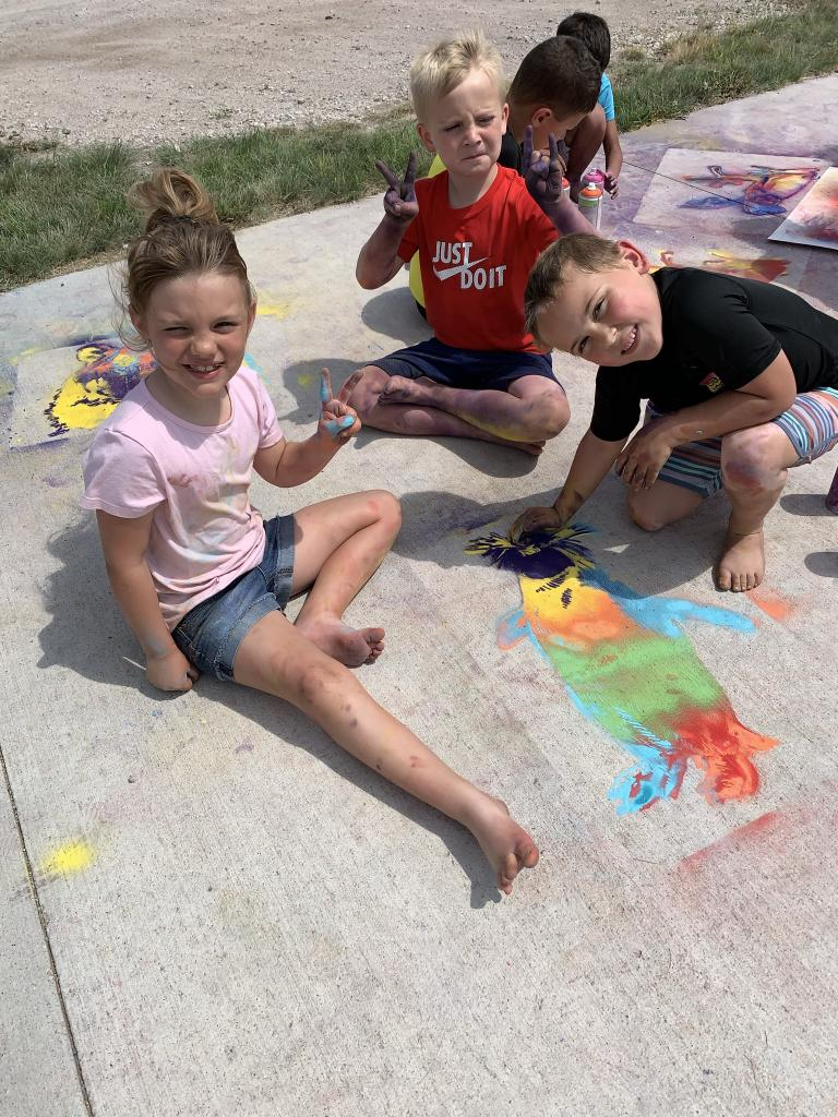 Students from the Alliance Recreation Center create spray chalk animals as part of the Stay Wild community arts project, led by Associate Professor of Art Sandra Williams. Courtesy photo.