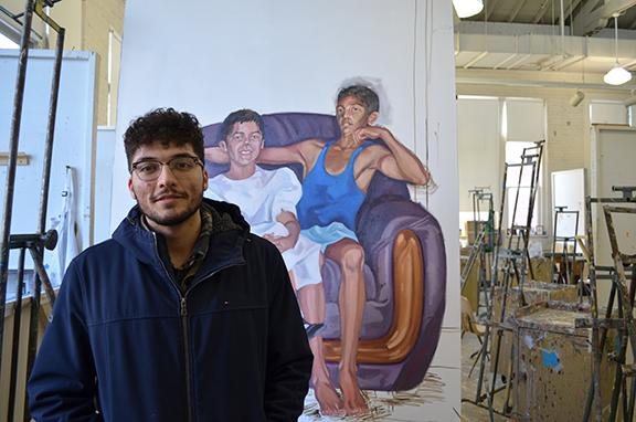 "Luis Martinez stands in front of his painting titled ""Flojeando,"" in the Richards Hall painting studio."