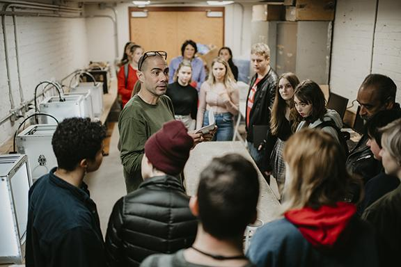 Associate Professor of Art Santiago Cal discusses the sculpture program with students from Lincoln Public Schools. Photo by Justin Mohling.