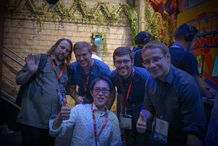 Brad Flick (second from left) with the other members of the creative team pose with Naoto Ohshima (front), Sonic's original creator.