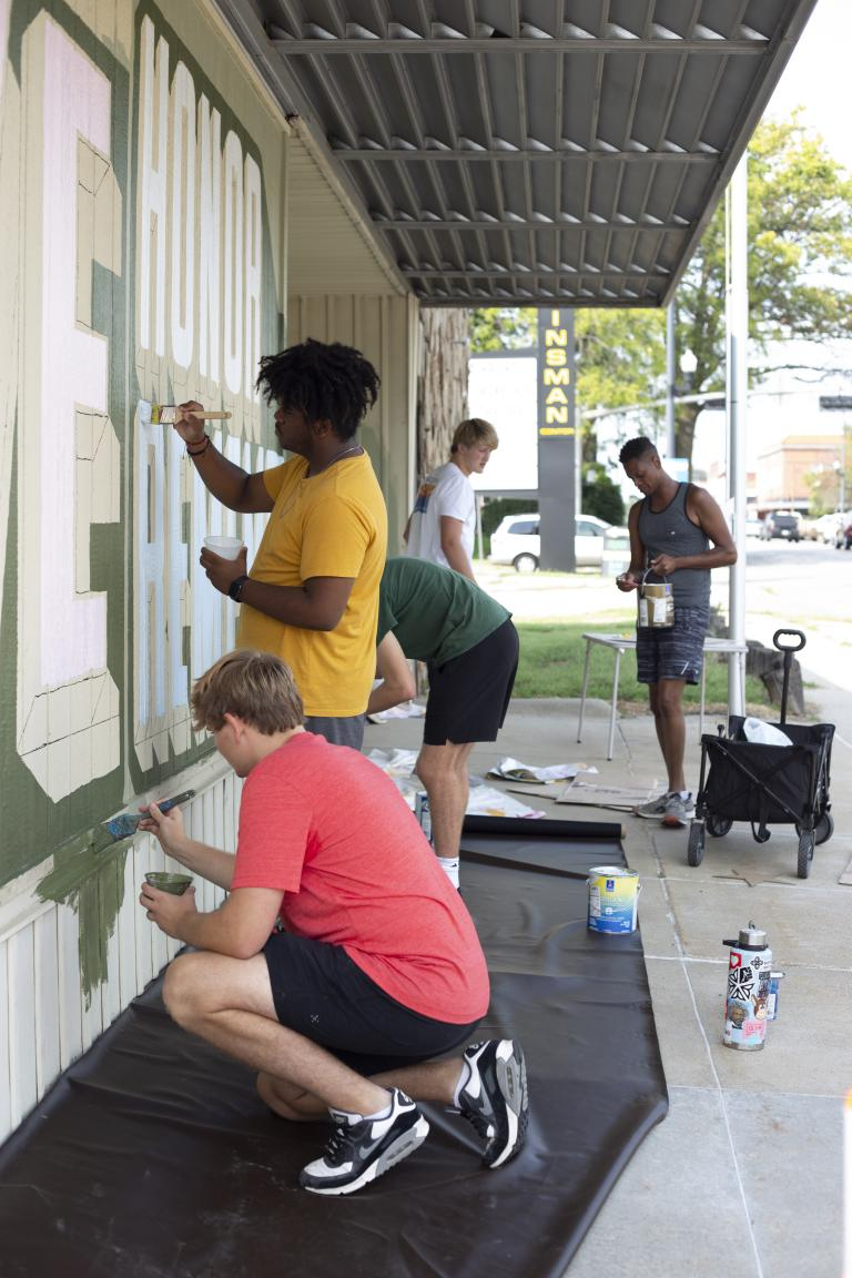 Students from Associate Professor of Art Sandra Williams' University Honors seminar Graffiti Revolution help Shawn Dunwoody (right) paint his mural at the Veterans of Foreign Wars at 2431 N. 48th St. Photo by Eddy Aldana.