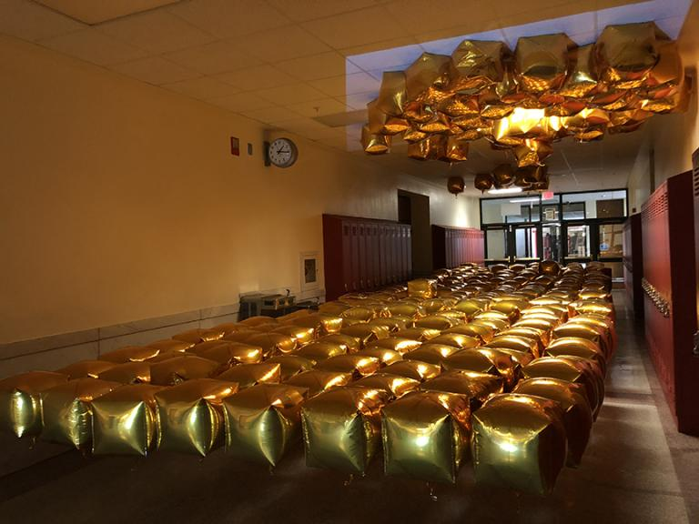 """Almost Disney"" was built with 270 gold mylar balloons attached to the floor by fishing line so they appared to float waist-high, along with projection and sound inside a hallway."