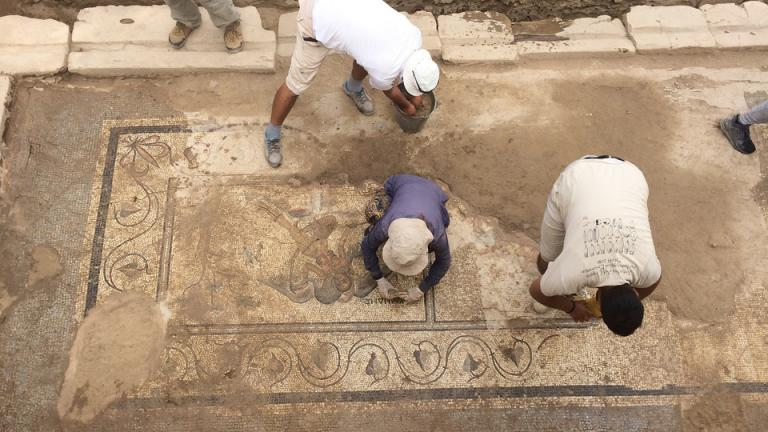 Turkish members of an excavation team led by Nebraska art history professor Michael Hoff sweep dirt away from a new mosaic discovered in August 2018. Courtesy photo.