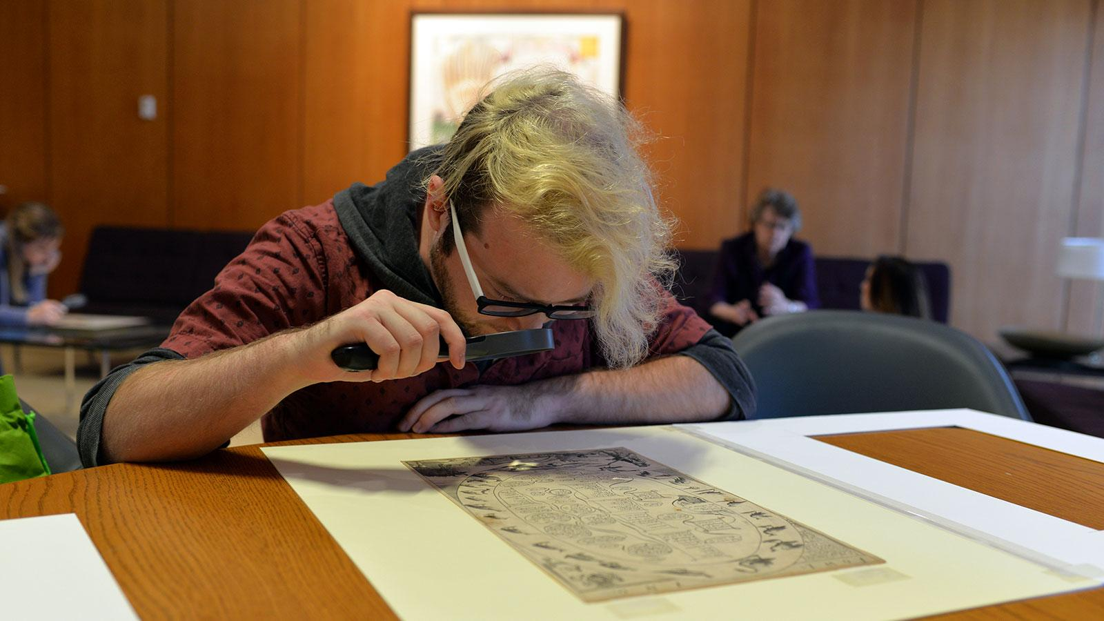 art history student looking at archival print through magnifying glass