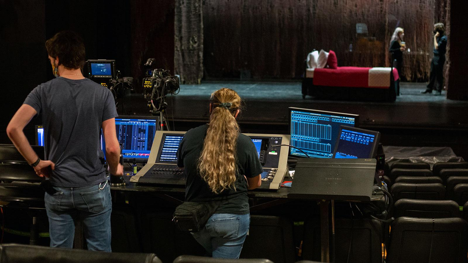 two design tech students work behind the scenes on audio while actors are on stage