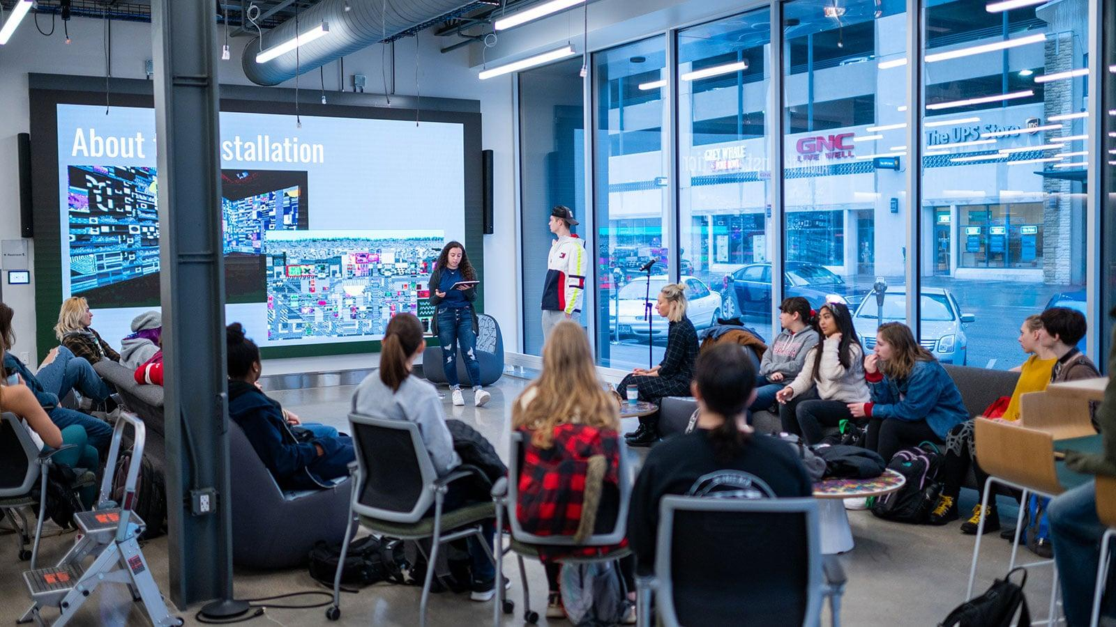 two emerging media students give a presentation in the Carson Center